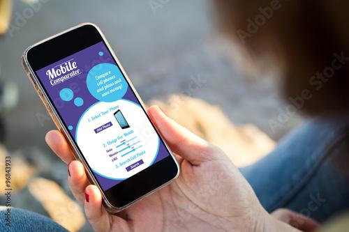 Foto  Frau, die auf der Straße hält ihren Smartphone mit beweglichem r sitzt
