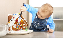 Cute Little Child Decorating The Christmas Gingerbread House