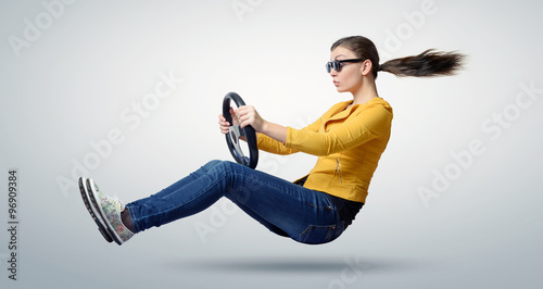 Obraz Young beautiful girl in sunglasses driver car with a wheel, auto concept - fototapety do salonu