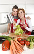 beautiful American couple working at home kitchen in apron mixing vegetable salad smiling happy