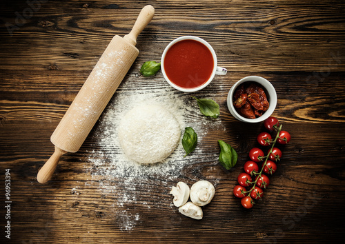 Foto  Pizza dough with ingredients on wood