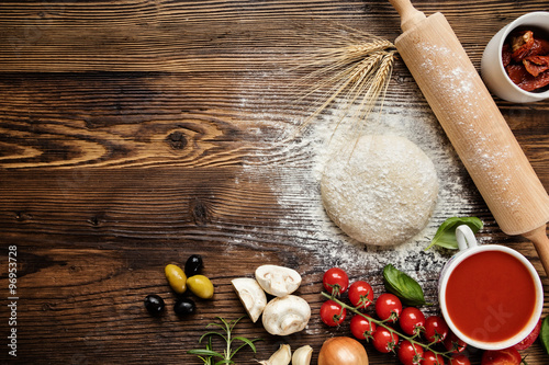 Foto op Canvas Pizzeria Pizza dough with ingredients on wood
