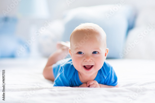 Baby boy in white sunny bedroom