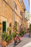 Fototapeta Uliczki - Idyllic alleyway with plants and moped