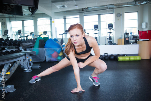 Foto op Plexiglas Fitness Pretty woman with red hair stretching before workout in gym