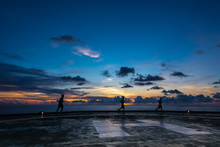 Three Men Running On Oil Rig Helipad In Sunset Time