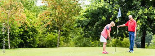 Deurstickers Golf Senior woman and man playing golf putting on green