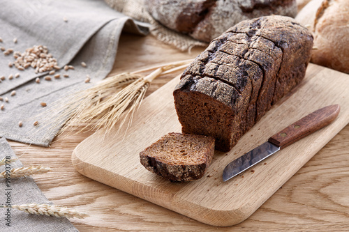 obraz dibond Sliced black bread on a wooden table