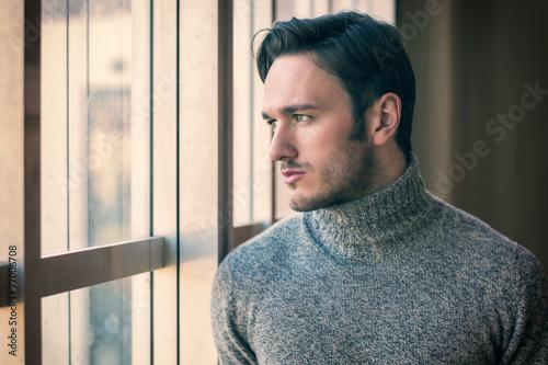 Fotografie, Tablou  Handsome serious man standing inside modern building