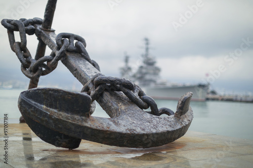Anchor on the embankment and the cruiser in the port of Novoross Fototapet