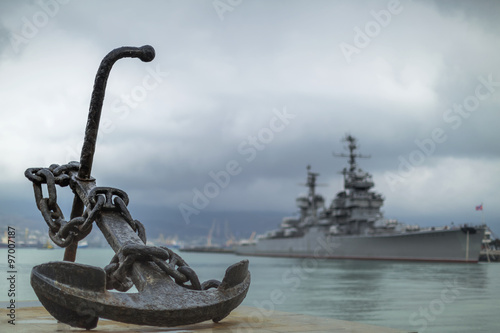 Photo  Anchor on the embankment and the cruiser in the port of Novoross