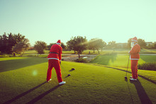 Two Santa Claus On A Golf Course