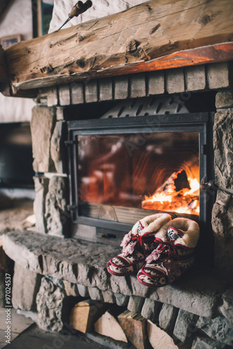 Fotografie, Obraz  Christmas comfortable slippers by the warm cozy fireplace