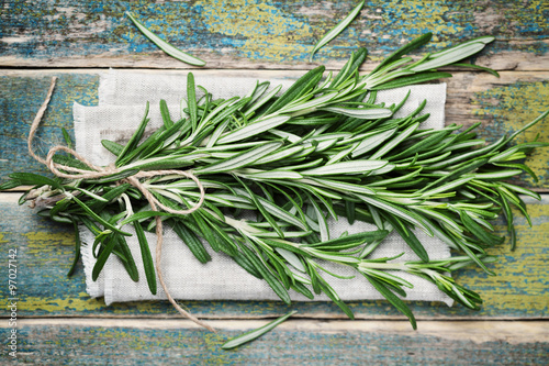 Fototapeta Bunch of rosemary on wooden table, rustic style, fresh organic herbs, top view obraz