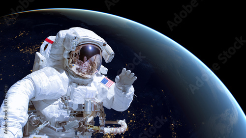 Poster Nasa Close up of an astronaut in outer space, earth by night in the background. Elements of this image are furnished by NASA