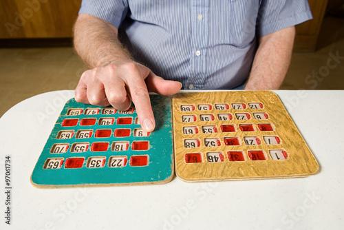 Senior man playing bingo плакат