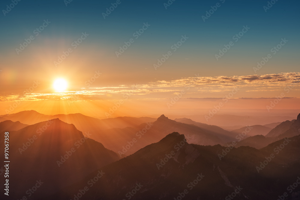 colorful sunset on top of austrian mountain alps