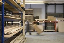Man Pushing Boxes In Warehouse