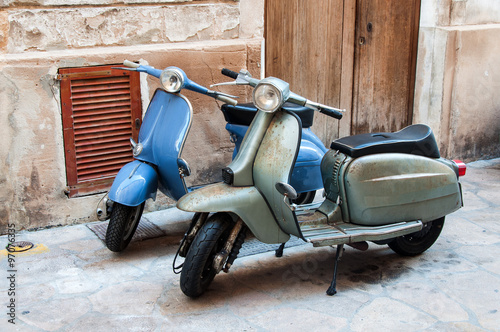 Two vintage scooter parked in the street Slika na platnu