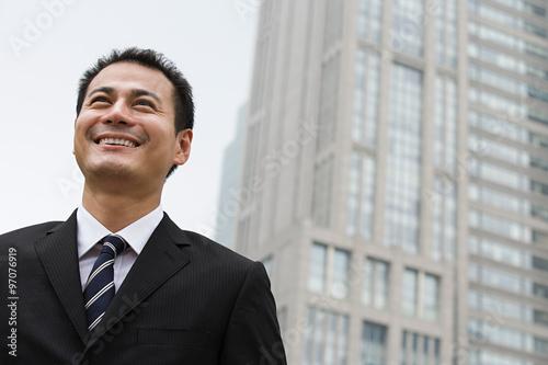 Smiling businessman near a skyscraper Poster
