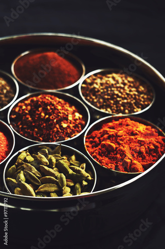 Printed kitchen splashbacks Spices Set of traditional indian spices in metal bowls on black backgro