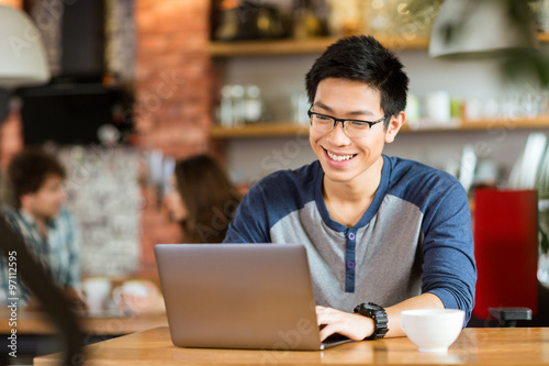 Foto  Happy cheerful asian male smiling and using laptop in cafe