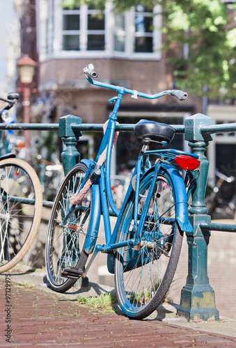 Deurstickers Fiets Parked blue bicycle on a railing in the historic canal belt, Amsterdam, The Netherlands