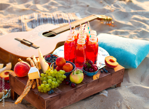 Fotobehang Picknick Picnic on the beach at sunset in the boho style