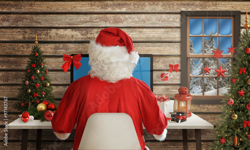 Santa Claus responds to letters on a computer for Christmas. Gifts, Christmas tree and decorations on table. #97143767