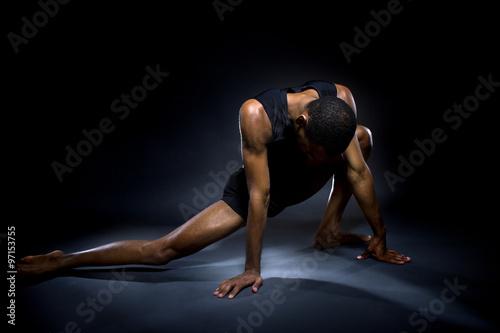 Fotografia  Black male dancer practicing warm up exercises for flexibility