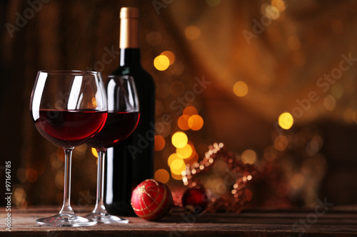 Foto auf AluDibond Wein Red wine and Christmas ornaments on wooden table on golden background