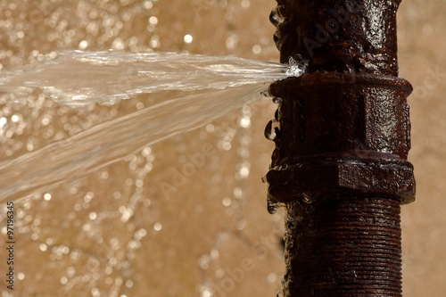 Fotografia  Rusty burst pipe squirting water at high pressure