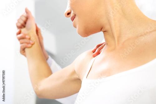 Fototapeta Masaż barku. Lekarz ortopeda bada ramie pacjentki  obraz