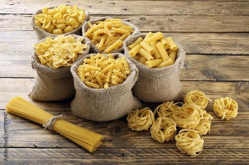 Foto pasta italiana grezza sfondo legno rustico
