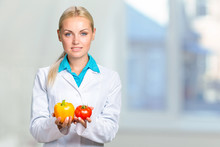 Portrait Of Happy Female Dietician With Fresh Vegetables And Diary