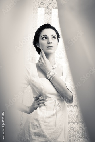 Photographie  Picture of elegant beautiful young lady in white dress looking up on copy space