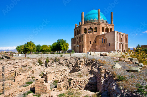 Ruins of stone citadel and historical mausoleum Dome of Soltaniyeh background. The structure, erected in 1312 AD in Iran.