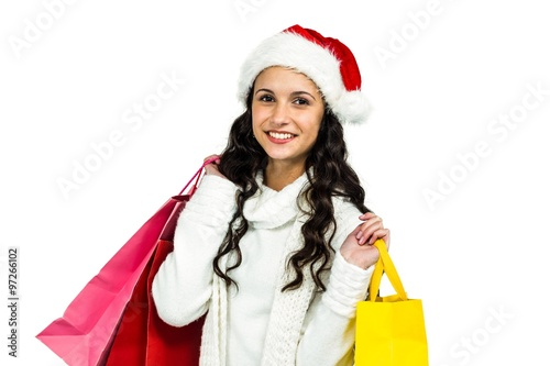 109fb2bc221ee Smiling woman with christmas hat holding colored shopping bags - Buy ...