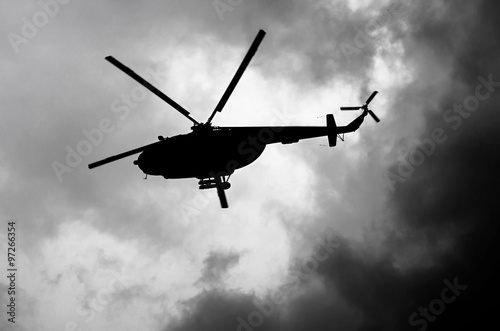 Tuinposter Helicopter silhouette of a helicopter in the clouds, black and white