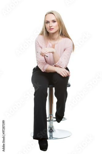 Fotografia, Obraz  Elegant beautiful woman sitting on a contemporary metal bar stool