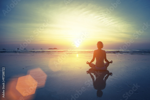Foto  Silhouette meditation yoga woman on the background of the sea and amazing sunset