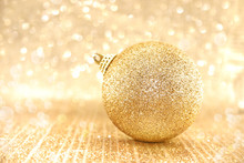 Golden Christmas Ball On Shiny Background With Copy Space For Te