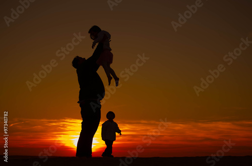 Fotografie, Obraz  Silhouette of a single father on vacation with his two kids