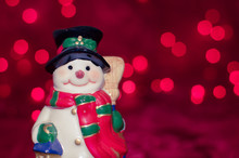 Ceramic Snowman On Red Bokeh Background