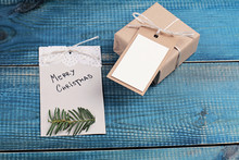 Merry Christmas Background. Christmas Vintage Gift Box With With Copy Space Blank Tag On Blue Wooden Background.