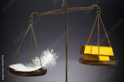 Fotografie, Obraz  The feather outweighs a stacks of golden bars.