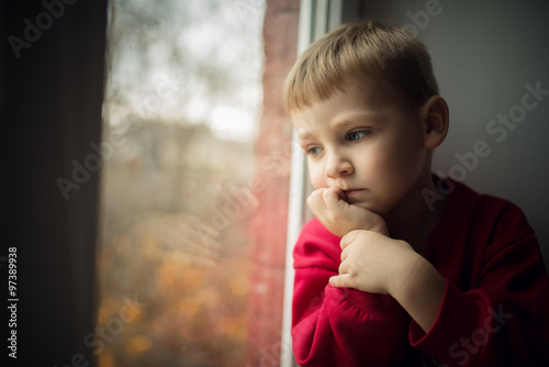 Fotografie, Obraz  small boy sitting near window and thnking about something