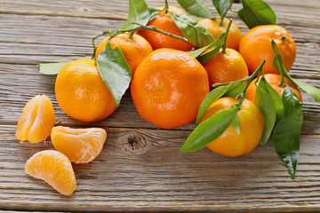 Mandarins with leaves on wooden background