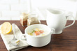 Delicious salmon cream soup on wooden table, which served with sliced lemon and spices