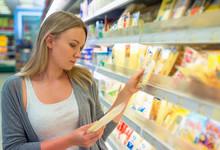 Woman Choosing Cheese In Groce...